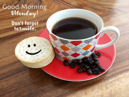 Morning coffee. Cup of black coffee and raw coffee beans with smiling face on cookies and text greeting - Good morning Monday. Do not forget to smile. On natural background of wooden table. Standard-Bild
