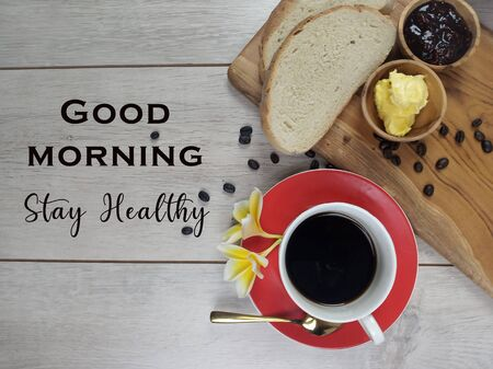 Good Morning. Stay healthy. An healthy morning greeting with food breakfast, a cup of coffee, brown bread, spoon, wooden cutting board, flower and roasted coffee beans on white wood table background.