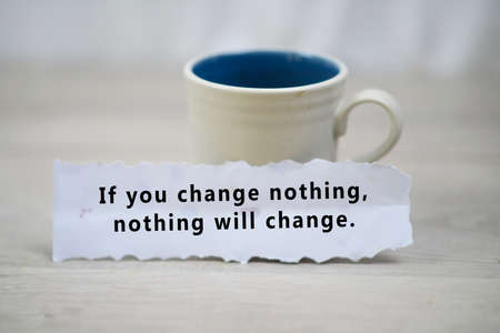 Inspirational quote - If you change nothing, nothing will change. A paper note reminder with motivational text message on it on white table background.