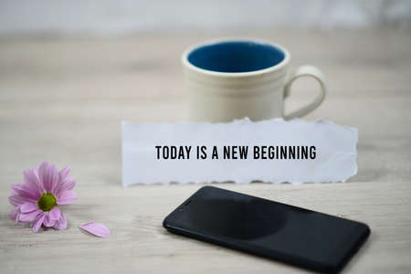 Inspirational quote - Today is a new beginning. With morning a cup of coffee, black smartphone and purple daisy flower on white soft blurry background. Motivational words concept. Banque d'images