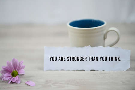 Inspirational quote - You are stronger than you think. With a cup of morning coffee and beautiful purple daisy flower on white wooden table background. Motivation words on paper note with motivating text concept.