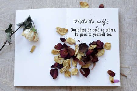 Note to self concept with motivational words - Do not just be good to other. Be good to yourself too. On background of dried roses petals scattered on white paper book. Still life concepts.