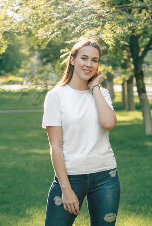 Portrait of one young beautiful European brunette in a trendy summer white t-shirt. Sexy carefree caucasian woman rejoices and smiles. Girl posing in sunny summer weather.