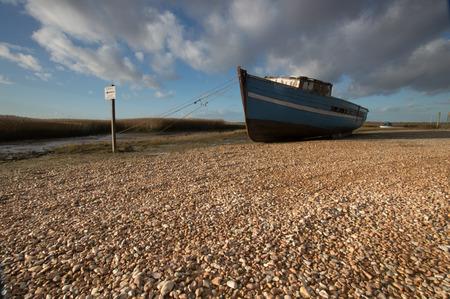 burnham: Boat in the pebbles, at low tide, at Burnham, Norfolk Stock Photo