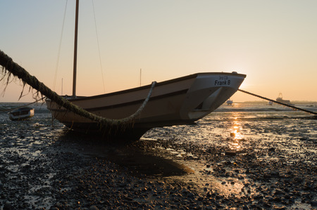 tethered: Tethered Boat at Leigh on Sea, Essex, at sunset when the tide is out.