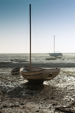 tethered: Boat in the mud at low tide, Leigh on Sea, Essex at sunset
