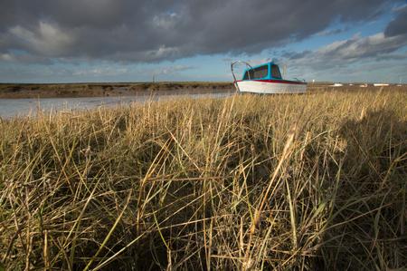 Boat stranded at low tide, at Burnham, Norfolk Stock Photo