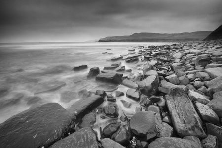 Cloudy Kimmeridge Bay, Dorset, England in black and white Stock Photo