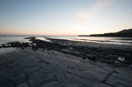 kimmeridge: Sun setting at Kimmeridge Bay, Dorset, England Stock Photo