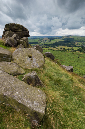 View from the top of a hill at Baslow Edge, in the Peak District, Derbyshire, with a mill stone in the foreground