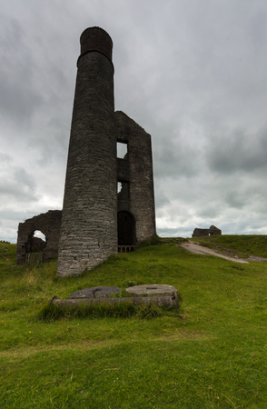 A chimney and some derelict buildings at a disused mine, Magpie Mine, in the Peak District Stock Photo