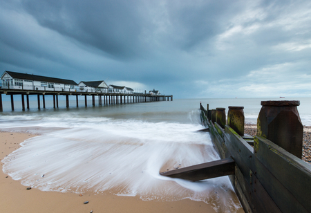groynes: A cloudy sunrise at Southwold Pier, in Suffolk Stock Photo