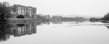 Carew Castle & Mill Reflecting in the water on a misty morning, Pembrokeshire Stock Photo
