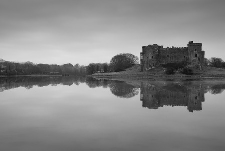 Carew Castle reflecting in the water on a misty morning, Pembrokeshire Stock Photo
