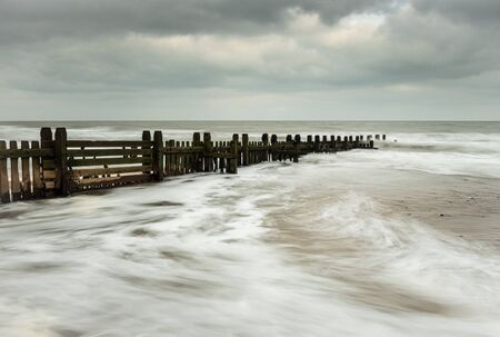 Groynes going out to sea on the beach at Happisburg, Norfolk Standard-Bild