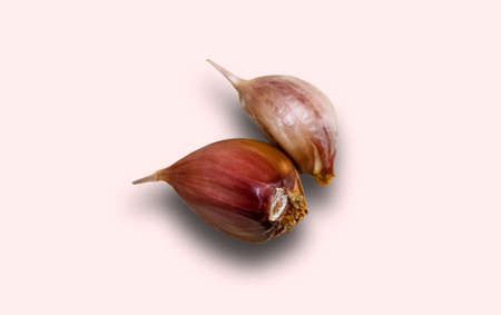 Two unpeeled garlic cloves on a white background with shadow. Close-up, selective shot. 스톡 콘텐츠