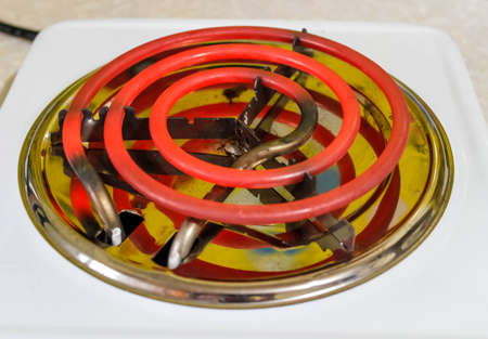 Red-hot metal spiral of an electric stove. Close-up, selective shot. Foto de archivo