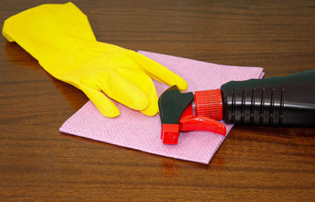 On the table are cleaning products, a rubber glove and a napkin. The concept of disinfection and cleaning.