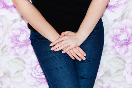 A woman in jeans holds her hands at the bottom of her stomach. Pain, urinary incontinence, gynecology