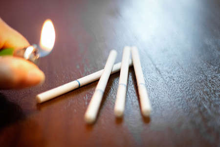 On the table are several thin cigarettes and a blurry lighter with a fire. Selective focus, blurred border.