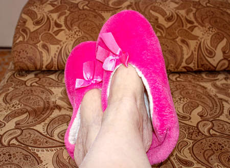 Women's feet are lying on the table with pink cozy Slippers on. Close up. Imagens