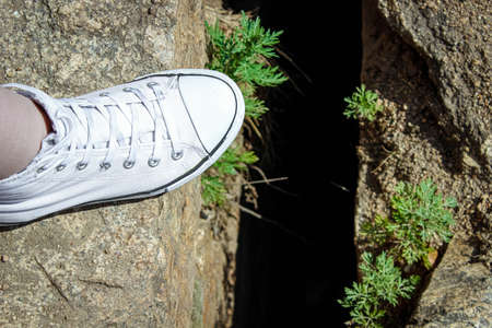 A woman's foot in white sneakers near a dark crack in the rock. The view from the top.