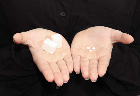 Choice - sugar Cubes and stevia tablets in your hands. Sugar substitute. Diabetes. 版權商用圖片