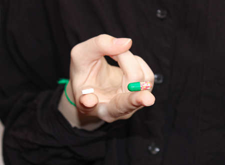 On the fingers of the hand are two different tablets. Choice of medicine or vitamins. Drink vitamins or get sick.