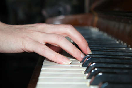 A woman's hand is playing an old piano. Close up. Standard-Bild