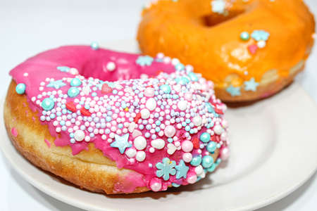Two delicious donuts on a plate decorated with decorative sprinkles. Close-up, selective focus.