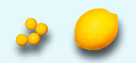 Whole lemon and round vitamins ascorbic acid with shadow on a light background. Close-up, horizontal frame.