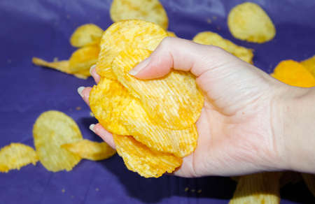 A woman's hand lifted an armful of potato chips from the dark blue tablecloth. Close up.