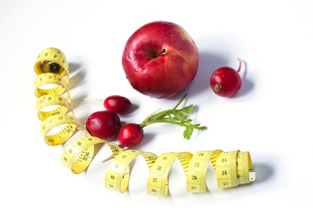 centimeters: red radishes, centimeters and apple on white background. Stock Photo