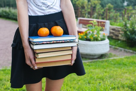 Female hands holding stack of books. Young girl with schoolbook. The concept of the beginning of the school year, student life