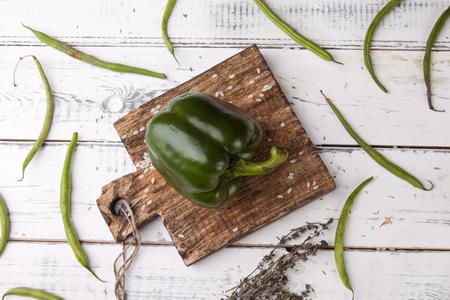 Green bell pepper on wooden cutting plank.