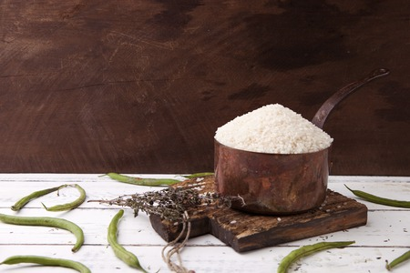 long bean: Rice in iron stewpan with green beans on wooden cutting plank. Copy cpace for text