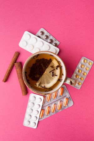 Herbal tea with lemon and pills . Healthcare Concept