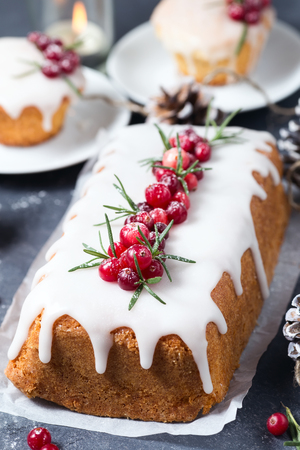 Christmas cake with sugar icing, cranberries and rosemary