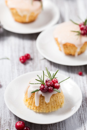 Christmas mini cake with sugar icing, cranberries and rosemary on a wooden table