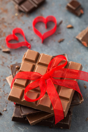 Valentine's day. Chocolate bars decorated red ribbon and hearts
