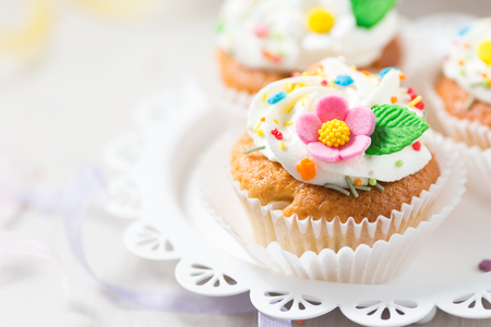 Easter cupcakes with white cream and sugar flowers