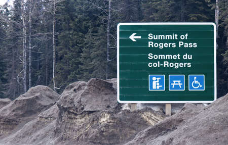 View of road sign with directional arrow points towards the Summit of Rogers Pass on Trans-Canada Highway