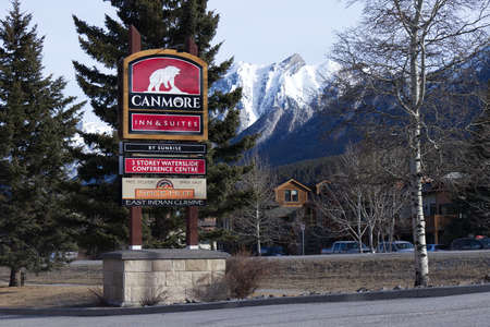 Canmore, Canada - April 20,2020: View of  entrance Canmore Inn and Suites Hotel with pine trees and mountains in the background