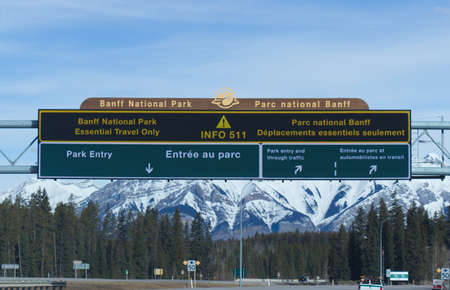 Alberta, Canada - April 20,2020: View of directional board at the entrance of Banff National Park on Trans-Canada Highway. Essential travel only.