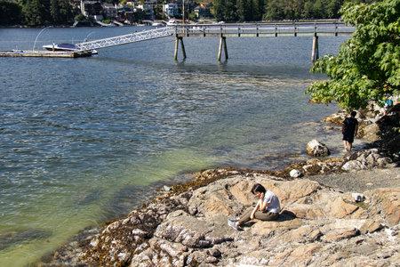Belcarra, Canada - July 13,2020: Girl is sitting on the beach in Belcarra Regional Park 新聞圖片