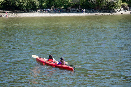 Belcarra, Canada - July 13,2020: Belcarra Regional Park full of people at sunny day. Girls kayaking on river.