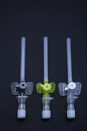 intravenous catheters on a black background, shot close-up. multicolored catheters have different diameters - from the smallest to the largest