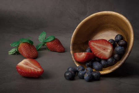 fresh strawberries and blueberries lie in a wooden plate. the plate is tilted so that several berries have fallen out of it and lie side by side. in the background are strawberries.