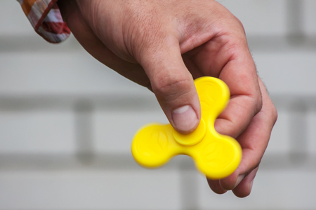 The man is holding a yellow spinner in his hand Stock Photo