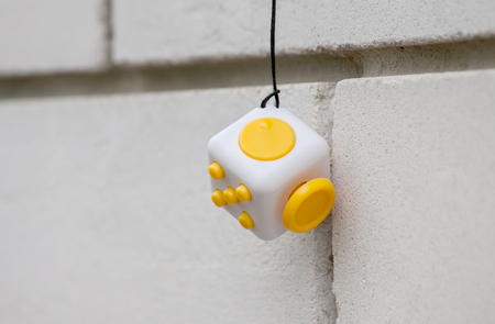 Yellow cube antistress on a brick wall background, Fidget Cube Simple Stress Reliever, Fingers Toy